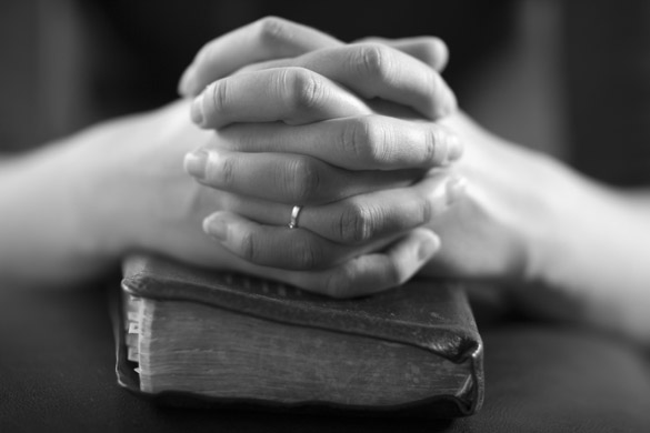 woman-folding-hands-over-her-bible-and-praying